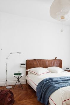 House tour: a pared-back 19th-century apartment in Paris : The bedhead made from a vintage leather gym mat; the 'Tolomeo Micro Terra' lamp is by Michele de Lucchi and Giancarlo Fassina for Artemide.