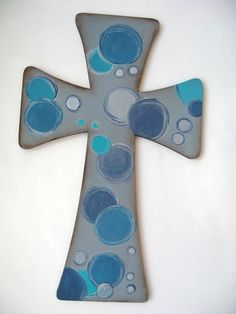 """This painted wood wall cross for your home is approximately 11"""" tall. It is 3/8"""" thick with a hanger on the back. It is hand painted with gray, blue and turquoise circles.    It is sealed for protection."""