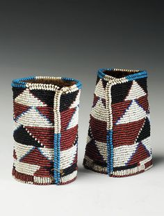 South Africa   Beaded cuffs from the Zulu people; hide applied with beads in a bands of triangular motifs in red, white, black and blue, each 13cm. high   408£ ~ sold (July '05)