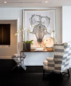 entry with modern console table and striped wingback chair. great art!