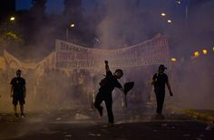 An anti-austerity protester throws a bottle at riot police in Athens, Greece