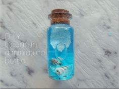 Bottle Charm: Ocean in a miniature bottle. Hey everyone! Here is a super easy tutorial on how to make a realistic looking oceansea in a bottle using items you probably already have at home! FYI: You can use cooking oil but because it is yellow it wont Glass Bottle Crafts, Diy Bottle, Bottle Art, Glass Bottles, Ocean Bottle, Bottle Jewelry, Bottle Charms, Bottle Necklace, Miniature Bottles