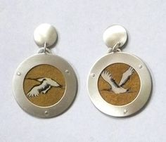 "Kathleen Faulkner: Earrings in sterling silver, watercolor, colored pencil, ink, paper, and mica. 1.5"" in diameter"