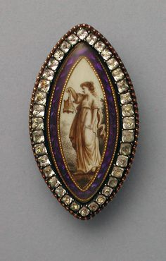 The sepia woman holding the lantern is 'lighting the way so that others may see' (an allegory to God) with her right foot forward and the foliage behind her. The difference in the clasp to the piece shows it was a later addition to a pendant.