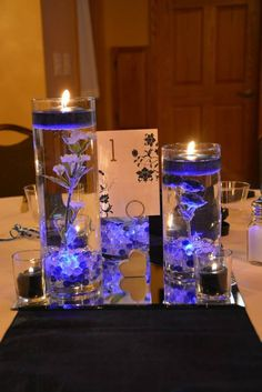 "There are 16 centerpieces. Each centerpieces has three vases (6"", 7.5"", and 10.5""). Each vase comes with a blue submersible LED, blue and clear glass marbles for the bottom, and one of three types of flowers (blue spray roses, white rose, or small white clustered flowers). Also included: 72 Glass votive holders + approx 26 navy votives, table numbers 1-20, 16 heart number holders. Not included: floating candles, square mirrors. These centerpieces were used for a wedding in October 2013 and…"