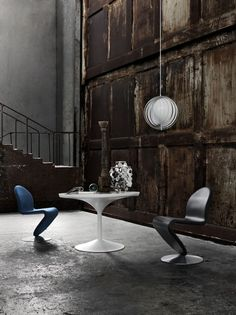 antique wooden panelling on concrete floor, accented by contemporary colorful furniture. cool.