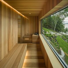 Upon entering is a service corridor that links the garage to the main house and provides access to a series of rooms, including a washroom, a laundry room, a workout area with large glass walls, and a sauna.