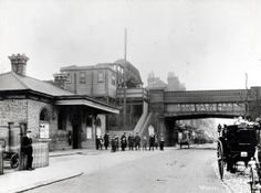 Turnham Green Underground station, District lines. Exterior view of the London & South Western Railway station, signage is displayed on the canopy above the entrance and also on the poster panels. Early large sized station name signage is displayed on the bridge.    Unknown photographer, Pre 1911