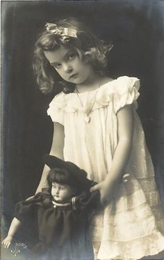 Vintage photo of hauntingly beautiful young girl with her doll, circa 1900…