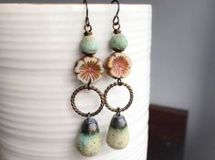 Long, bohemian style earrings in soft vintage shades of pale green, cream and bronze. They feature beautiful ceramic drops, handmade by bead artist Petra Carpreau (Scorched Earth), in soft pastel shades with a shimmering crackled glaze. The drops simply dangle from Vintaj brass twisted rings, with rustic Indonesian lampwork beads and Czech glass table-cut flowers above. These statement earrings have small hand antiqued brass French hook earwires by Patina Queen, and measure approximately 7…