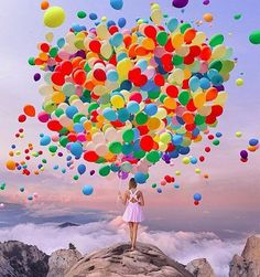 colorful balloons with girl on top of mountain