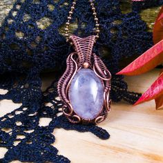 Handmade vintage necklace; wire wrapped copper pendant with rose quartz; oxidized antiqued copper wire and natural gemstone jewelry. 1 3/4 X 1 1/4 inch ( 4.3 X 2.7 cm ) Pale blue rose quartz cabochon captured in hand woven antiqued oxidized copper wire. Organic design Art Nouveau inspired.