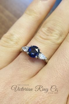 The vibrant blue sapphire engagement ring in platinum is is set with two pear shaped diamonds. The combination of the gemstones creates a elongated oval shape. This geometric shape was used during the Art Deco era of the 1920s and 1930s. #artdecoengagementring #bluesapphireengagementring #sapphirering #pearshapediamond #geometricringdesign