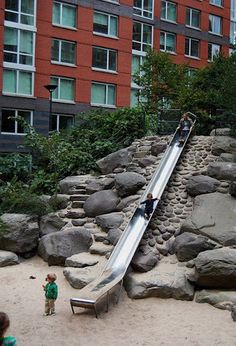 Teardrop Park, Manhattan, New York. There are rocks here for kids to climb on to get to the top of the slide, and other rocks around the park for climbing.