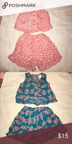 Two two piece shirts and shorts Both in great condition, a little worn. One is Adorable pink, purple buttons, and nice floral pattern, great summer outfit!! The other is a nice dark blue with floral print. Both perfect for summer!! Matching Sets