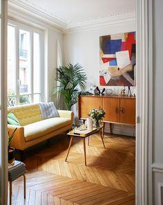Un séjour à l'ambiance rétro, entre parquet point de Hongrie, canapé jaune poussin et mobilier 50's