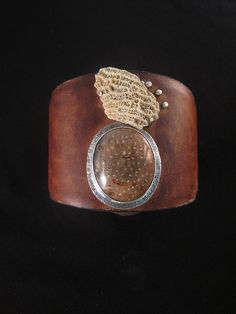 e-bu-jewelry by Robbin Smith and Warren Moeller, sterling silver, fossil palm, found coral leather cuff