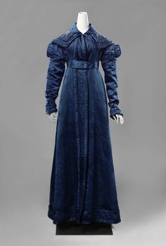 Rikjs Museum, item BK-16000, c1820 Redingote of blue satin, lined with cream silk with thick interlining. Smooth double collar. Long sleeves that fall on the hand, decorated with puff sleeves. Attached waist belt ends are decorated with knot and tassel trims.
