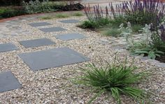 Hardscape material idea for hell strip or back path to patio... blue stone tiles set in pea gravel, with plant borders set off by cobblestone.