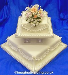 Square Ivory Wedding Cake with delicately coloured sugar flowers, lace effect frills & satin bows Wedding Cake Icing, Ivory Wedding Cake, Wedding Cake Images, Square Wedding Cakes, Diamond Anniversary Cake, Anniversary Cakes, Colored Sugar, Baby Doll Accessories, Wedding Cake Decorations