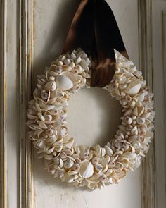 "Shell Wreath Centerpiece - Whether you hang it on a wall or use it as a centerpiece, this shell wreath will add a natural element to your holiday decor. Imported.  Made of natural shells on a wood frame.  Some shells have iridescent finish.  19.25"" diameter x 3.5"" deep ($195.00)  I like how some of the clam shells have been used whole and open."