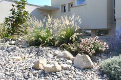 Sur ce massif rocailleux et sec se succèdent, de gauche à droite, un magnolia, deux graminées, un abelia grandiflora, un perovskia (qui fleurit plus longtemps que la lavande) et une santoline, à la floraison jaune. Le choix de certaines vivaces vient de l'envie de fleurs des clients de Violette Egon. Elles sont adaptées à un jardin sec, permettent un jeu de couleurs et offrent une floraison qui dure le plus longtemps possible.