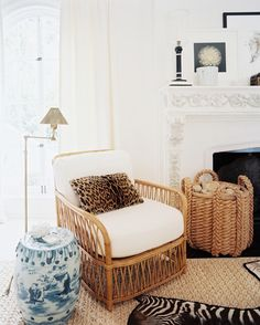 French Photo - A natural fiber rug, a blue-and-white garden stool, and a leopard-print pillow in the corner of a living space