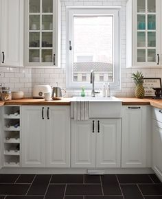 Bright corner sink A timeless white palette. A wall white tiled Metro style replaces the painting and it is also useful as a backsplash. A wooden counter is resistant and provides a warm touch. Photographer: André Rider Source: House & Home October 2012