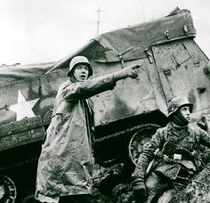1944, Battle of the Bulge: A major German offensive against Allied forces in the Ardennes, December 16-January 25, 1945, is the bloodiest battle fought by the US in World War II. German soldiers advance past a knocked-out US halftrack.