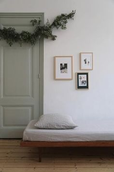 wooden floors, daybed, pale sage green door, branch decoration, small gallery wall