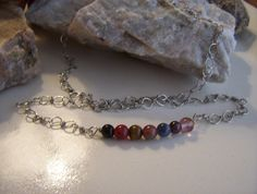 Men's / Unisex Silver Plated Chakra Necklace by AlisonsGemstones on EtsyAchieving personal peace and balance using the energy of a variety of natural stones to represent the 7 energy centers  Root - red / black  Sacral - orange  Naval - yellow  Heart - green/ pink  Throat - blue  Forehead - Indigo  Crown - purple/ crystal   This Necklace uses Obsidian, Carnelian, Tigereye, Kashgar Garnet, Sodalite, Amethyst and Fluorite. The chain is hand wrapped Silver Plated wire