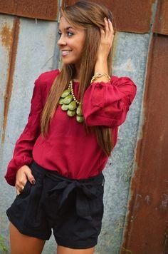 Burgundy shirt, black shorts, olive green necklace