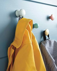 """If your entryway has a windblown look -- kids' coats strewn on the floor, bags dropped willy-nilly -- mount a series of knobs at kid-friendly heights to eliminate their bleating, """"But we can't reach!"""" These wooden hangers (actually, drawer knobs painted different colors) look modern and fresh, not childish, and their rounded edges make them safe for little noggins walking nearby."""