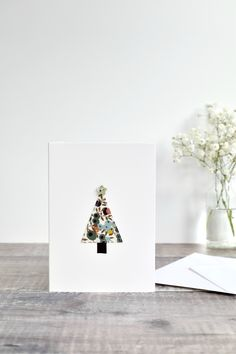 Liberty fabric Christmas tree card. A simple but elegant Christmas card made using pretty Liberty fabric with green berries. The fabric is stitched directly onto the card to create an embroidered Christmas tree. On top of the Christmas tree is a small pearlescent star button. A lovely card to give to a special person at Christmas time. #libertyfabric #christmascard #christmastreecard #sewnchristmascard #stitchedchristmascard #embroideredchristmascard #sewncard #embroideredcard #stitchgalore Fabric Christmas Trees, Handmade Christmas Tree, Christmas Cards To Make, Elegant Christmas, Christmas Time, Christmas Decorations, Fabric Cards, Liberty Fabric, New Year Card
