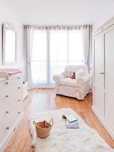 Exemple d'une grande chambre de bébé neutre nature avec un sol en bois clair et un mur blanc.