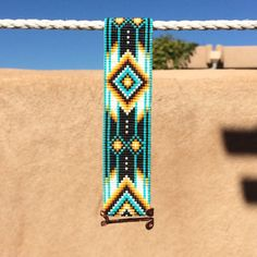 This Squash Blossom Bead Loom bracelet was inspired by all the beautiful Native and Latin American patterns I see around me in Albuquerque, New Mexico. As with all my pieces, Ive created it on a bead loom with great care and attention to detail. IMPORTANT NOTE: Please measure your wrist carefully before order placement, to ensure a proper fit. These bracelets are not adjustable.  The beads used in this piece are my favorite - high quality glass Japanese Delicas, much more even and consistent…