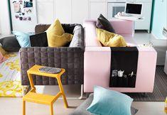 Ein graues Sofa und ein KLIPPAN 2er-Sofa Kimstad hellrosa, Rücken an Rücken in der Mitte eines Wohnzimmers platziert.