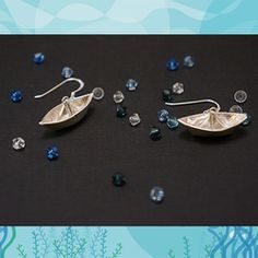 "These Origami Boat earrings are made of fine silver (.999 silver) and adjoined with sterling silver fishhook earrings. Each little boat was meticulously handcrafted out of a silver PMC sheet and fired in a kiln at 1650 degrees fahrenheit for 2 hours for maximum strength. Upon close examination you can see the great care and effort that was put into neatly folding each boat. The Origami Boat earrings are 1""W x 3/8""H and hangs about 1"" from the earlobe."