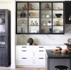 Black and white kitchen with glass front cabinets and marble backsplash