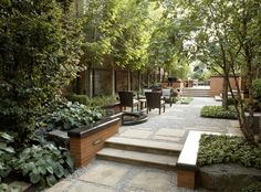Patios & Decks - Scott Byron & Co. - Contemporary terrace with flagstone steppers in mixed gravel and flagstone steps with brick seat walls with polished black granite coping in urban garden