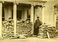 """From UCD Digital Library, Desmond FitzGerald Photographs, Photograph by W.D. Hogan: """"the front porch of an imposing building which has been heavily fortified with sandbags; an Irish Free State Army soldier is standing on guard; three others are peeping over the sandbags."""""""