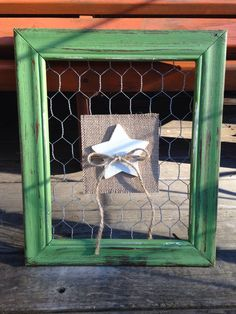 Painted and distressed picture frame backed with chicken wire with a removable wood painted white star placed on burlap paper in center of the frame. Frame measures 12 inches high and 10 inches in wid