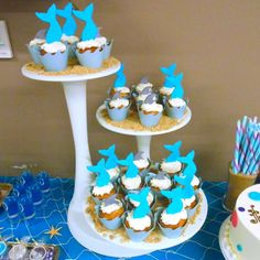 """Basic cupcakes were transformed to perfectly match our theme when topped with beautiful fondant Mermaid Tail & Shark Fin Cupcake Toppers and accented by Ocean Wave Cupcake Wrappers. These cupcakes sat upon a bed of crushed graham cracker """"sand"""" on an incredible three-tier cake stand."""