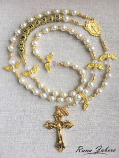 This simple, yet elegant Rosary features 6mm off-white pearls, accented with Angel beads with gold wings for the Our Father beads. The beautiful cross has a gold finish that shines in the light. On ea