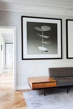 Duże, przeskalowane obrazy/grafiki na ścianach. Zestawienie bieli, czerni, delikatnej szarości z drewnem w odcieniach złota (mebel i podłoga)