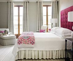 Soft Gray + Hot Pink Hot pink is a standout against warm gray walls and white linen. The uncluttered aesthetic combines just enough ruffles and pleats with the right amount of contemporary notions for a sophisticated feminine retreat. Here, color takes precedence over frilly accents. To maintain the crisp feel, walls are upholstered in the same fabric as window drapery. The tufted headboard makes an elegantly dramatic statement.