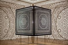 Intersections by Pakistan-born Anila Quayyum Agha  Laser-cut black lacquer wood cube suspended from the ceiling and lit with a single light bulb that casts breathtaking 32-feet-by-34-feet shadows to create instant architecture in an otherwise empty room.