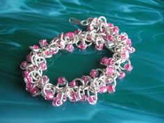 This beautiful feminine bracelet was made using non-tarnish silver enameled copper rings and pink-lined clear Czech glass triangle beads. Its finished using a silver-plated lobster claw clasp. Its made using the shaggy loops chainmaille weave.    It is 7 1/4 inches in length but can be adjusted up to 8 1/2 inches. Anything over 8 1/2 inches is a custom order and can be arranged.    I accept Paypal and Direct Checkout. Merchandise paid for with a Paypal E-check will not ship unt...