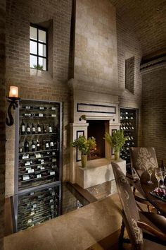 old world brick dining room with grand stone fireplace, wrought iron light fixture, dark wood dining table, wine cellar. Glass floor