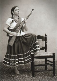 This is La Adelita , the lady of the revolution. She was during Mexican revolution as the leader of women. Today, during the celebration women dress in similar suits in honor of Adelita . Mexican Revolution, Pancho Villa, Mexican Heritage, Brown Pride, Female Soldier, Le Far West, Mexican Art, Mexican Girls, Badass Women